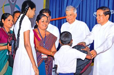 President Maitripala Sirisena and Prime Minister Ranil Wickremesinghe attended the Presidential Mobile Service at the Siri Dhamma Vidyalaya, Labuduwa, Galle yesterday. Here the President Sirisena presents gifts to schoolchildren. Pic: Sudath Malaweera