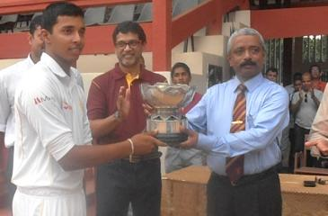 Ananda College principal S.M. Keerthiratne returns the L.D.H. Peiris memorial trophy to Royal captain Helitha Vithanage.