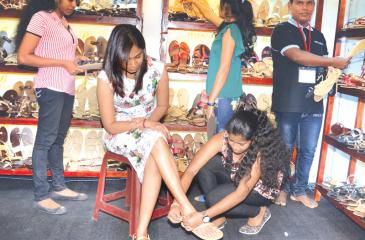 Footwear and leather - A girl tries out a pair of sandals at the Footwear and Leather Fair '17 which opened at the BMICH on Friday. The exhibition concludes today. PICTURE BY VIPULA AMERASINGHE