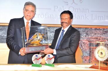 LOLC Group Managing Director and CEO Kapila Jayawardena presents a memento to Pak Oman Microfinance Bank Limited Chairman Yahiya Al-Jabri.