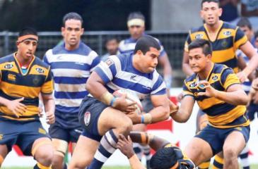 St. Joseph's College prop forward Shavon Gregory (ball in hand) barging through Royal hooker Hamza Barrie who is on the ground trying valiantly to stop him in the Singer 'A' division inter-school league rugby match played at the Royal Sports Complex yesterday. (Pic by Chintaka Kumarasinghe)