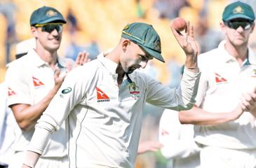 Australian spinner Nathan Lyon shows the ball with which he scalped eight Indian batsmen as he is cheered by team mates at the end of the innings on the first day of the second Test at Bangalore on Saturday. AFP