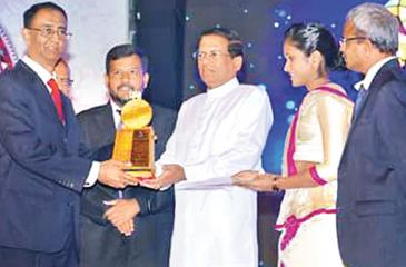 President Sirisena presents an award to a winner. Minister of Industry and Commerce Rishad Bathiudeen looks on.