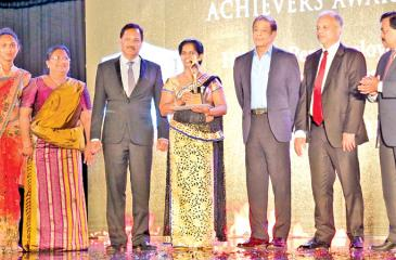Chairman, People's Bank Hemasiri Fernando presents the gold award to an official of the Delgoda branch which achieved the Gold award for highest per employee based business performance. Chief Executive Officer/General Manager, N. Vasantha Kumar,  Deputy General Manager, Channel Management,  Bonifus Silva look on.