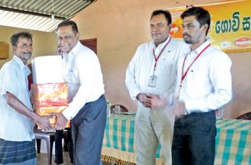 Shammi Karunaratne, Director/Chief Executive Officer – Plenty Foods handing over the provisions to a farmer in the presence of Vasantha Chandrapala, General Manager and Preethiviraj, Agriculture Manager of Plenty Foods.