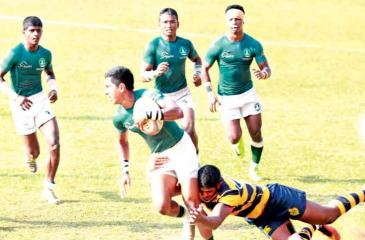 Isipathana vice captain cum full back Chamod Frrnando (ball in hand)  trying to evade a tackle from Royal captain and fly half Ovin Askey.  Also in the picture is Isipathana scrum half Harith Bandara (externally  left of Chamod