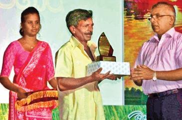 Executive Director / CEO - CIC Seeds, Waruna Madawanarachchi presents an award to a farmer