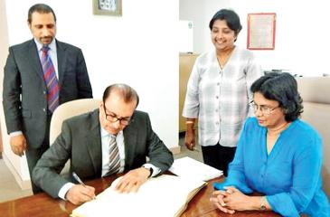 The UAE Ambassador Abdulhamid Abdulfattah K. Al Mulla signs the Visitors' Book at the Chamber. CEO of the Chamber, Dhara Wijayatilake, Sr. Asst. Secretary General Ms. Lilakshini de Mel and an UAE official look on.