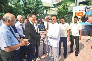 Chief Representative of JICA Sri Lanka Office Fusato Tanaka, hands over the keys to the  Minister of Higher Education and Highways Lakshman Kiriella.