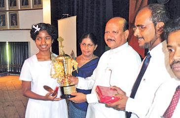 Picture shows Samithi receiving a cup and a cash award presented by the  Peoples Bank, from the Chief Minister Sarath Ekanayake. Principal Indra Withanachchi,Peoples' Bank Manager, Emil Mendis and Zonal Director W.M.Wijeratne are also in the picture.