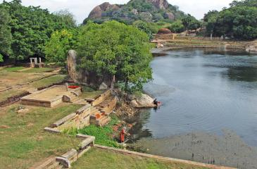 The Kaludiya Pokuna and the view of the monastic complex surrounding the pond. The Rajagirilena hill stands in  the background.