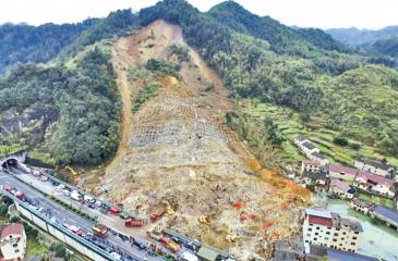 A aerial view shows rescuers searching for survivors among debris at the site of a landslide
