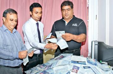 Weekly reader's winning coupons. From left: Gamini Ramanayake ( Pictures Editor, ANCL), Eranda Vithanage (Manager, Treasury) and D.S.llesinghe ( Senior Manager Sales) picking the winning coupons. Picture by Saliya Rupasinghe