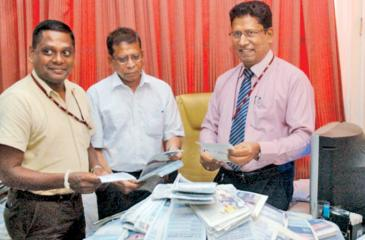 From left: Suresh Dematapitiya (Head of Sales, Lake House Connect (Pvt) Ltd, Ben Roche ( Sub Editor, Sunday Observer) and Chanaka Liyanage (Manager Channel /Publicity) picking the winning coupons.  Pic. Shan Rambukwella