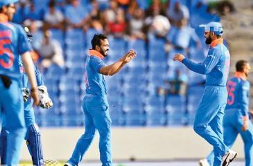 The Indians celebrate after dismissing a Windies batsman