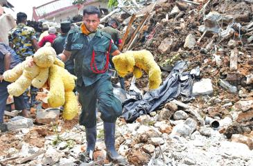 Sri Lankan Army soldiers walk past damaged houses after the collapse of a garbage dump in Meetotamulla, on the outskirts of Colombo on April 17, 2017. AFP