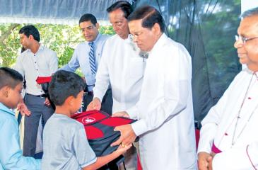 President Maithripala Sirisena presents books and bags to students. Auxiliary Bishop of Colombo Emmanuel Fernando, Minister John Amaratunga and Dinesh Weerakkody are also in the picture.