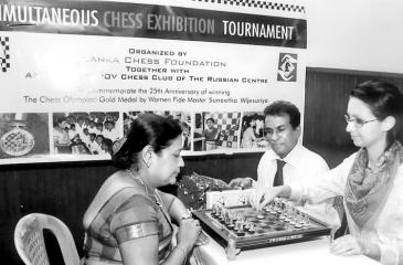 Mrs. Anastasia Khokhlova(right) is making her  first  move at  the  exhibition  chess match against Suneetha Wijesuriya at  the inaugural function held  at  the Russian Centre  watched  by Buddhapriya Ramanayake , CEO Russian Centre, Colombo.