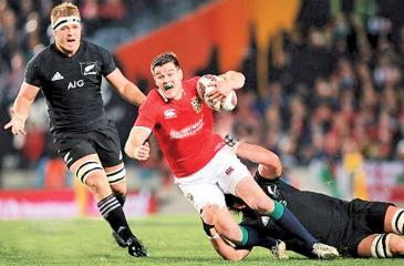 New Zealand's lock Sam Whitelock (R) tackles British and Irish Lions fly-half Jonathan Sexton during the third rugby union Test match between the British and Irish Lions and New Zealand All Blacks at Eden Park in Auckland - AFP