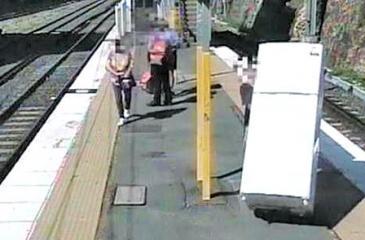 A man wheels a refrigerator across the platform at an Australian train station before boarding a commuter train. Screenshot: Queensland Rail/Facebook