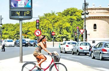 A cyclist waits to cross a road next to a thermometer showing 41C in Valencia, eastern Spain.  Pic: Manuel Bruque/EPA