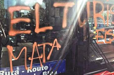 Four hooded men attacked a city tourist bus in Barcelona last week. They spray-painted 'Tourism kills neighbourhoods' on the windscreen as they shouted abuse at passengers. Pic: AB1/Solarpix.com