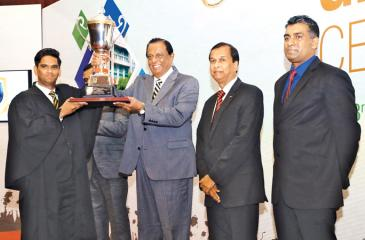 A student receives a trophy from Minister Amaratunga.