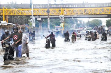 Pic: Rehan Khan/EPA People make their way through flooded streets after a heavy downpour in Karachi  on Thursday.