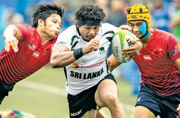 Lankan skipper Sudharshana Muthuthanthri tries to break through the defense of two Malaysians during the Plate Champion Final which was worked off yesterday in Hong Kong