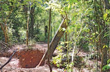 Vandalism: the hole dug to remove  a stone pillar by treasure hunters