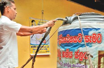 Warnasooriya  with a purified water tank