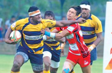 Army Sports Club's Number Eight Manoj Silva warding off a tackle from CH and FC's Avishka Lee in their Diolog 'A' division league Rugby match played at the Race Course yesterday which Army SC won 20-15    Picture by Hirantha Gunathilake