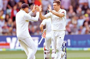 England bowler Chris Woakes (R) celebrates with captain Joe Root (L) after dismissing Australian batsman David Warner.- AFP