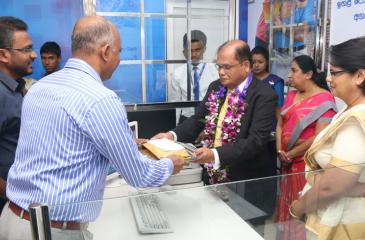 Commercial Bank Chairman Dharma Dheerasinghe (third from right) accepts the first deposit from a customer at the opening of the Bank's Rambukkana branch.