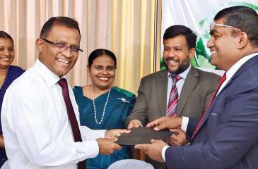 Pic: Chinthaka Kumarasinghe  Industry and Commerce  Ministry Secretary K.D.N. Ashoka (second from right) exchanges the green loan agreement with a BOC representative (second from left). Minister  Rishad Bathiudeen and State Minister Champika Premadasa (far right) look on.