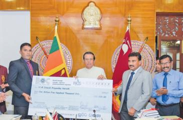 President Maithripala Sirisena handing over the cheque to Dinesh Priyantha.