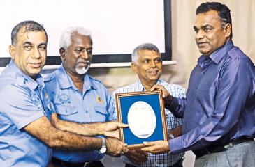 Ashhar Hameem hands over the memento to Base Commander of the Katukurunda Base Mohan Balasooriya. Also in the picture are Andrew Silva Secretary SMSC and Lion Wasantha Weerasekera.
