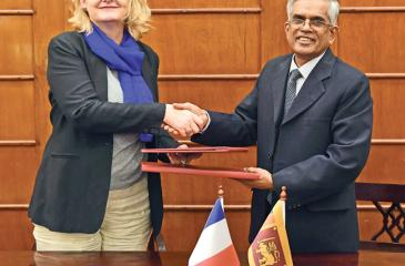 Secretary to the Ministry of Finance and Mass Media, Dr. R. H. S. Samaratunga and Chargé d'affaires of the Embassy of France in  Sri Lanka, Isabelle Miscot exchange the agreement