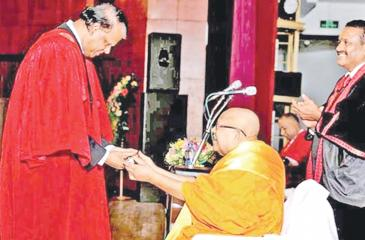 Thripitaka Vagishvaracharya, Mahopadhyaya, Pandith, the Most Ven. Welamitiyawe Dharmakirthi Sri Kusala Dhamma Thera, the Chief Prelate of the Colombo and Chilaw regions and the Chancellor of the University of Kelaniya, presenting the doctorate to Dr. Sena Yaddhige.