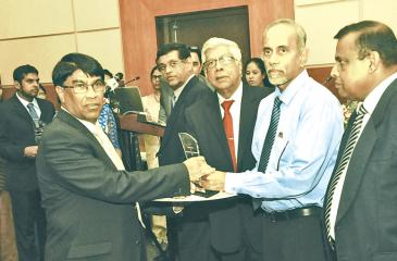 Senior Research Consultant Dr. Sumith Abeysiriwardena  receives the award from Chairman, SLCARP, Dr. Gerry Jayawardena. State  Secretary, Ministry of Agriculture, Bandulasena and Secretory, Ministry  of Agriculture, B. Wijayaratne look on.