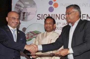Patrick Lim and Dr. Sayura Samarasundara exchange agreements. Minister Dr. Senarathne looks on.