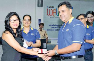 HNB's Deputy General Manager, Retail Banking, Sanjay Wijemanne presents the offer letter for a personal loan to Abirami Ledshumanan at the Wellawatte Customer Centre. S Narenthiran, Senior Manager, Wellawatte Customer  Centre is also in the picture.
