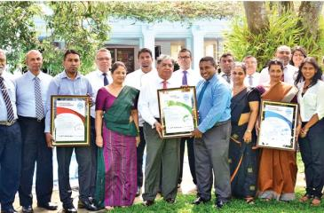 CCC CEO Sanith de Silva Wijeyeratne hands over certificates to MRH Managing Director Jayantha Panabokke, with the Senior Management Teams of MRH, CCC and SFG in the background