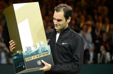 Roger Federer poses with the trophy after defeating Robin Haase of the Netherlands 4-6, 6-1, 6-1 to regain number ranking at the age of 36. - AFP