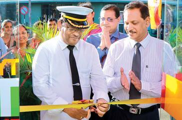 Chief Station Master K.S. Ananda Fernando opens the ATM.