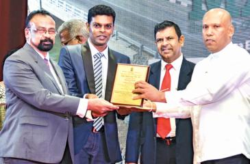 Deputy General Manager, Construction of Maga Engineering, Nihal  Chandrasiri (left) and Project Manager Sampath de Silva (AB019 project) receive the National Award for Construction Performance for rehabilitating and improving up to 10 kms of the Jaffna-Pannai-Kayts Road, from Deputy Minister of Housing and Construction Indika Bandaranayake.