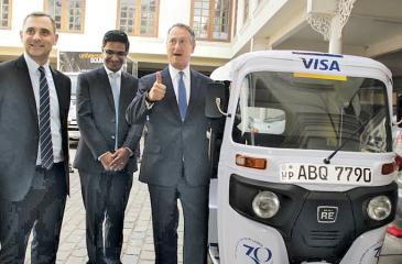 Visa officials with one of the 30 three-wheelers used in the promotional campaign