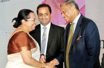 Ms. Shreema Vithanage receives her award from Chairman, SLI,  Hemaka Amarasuriya while DGM – HR and ER Rohitha Amarapala look on.