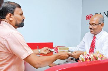 K. L. G. Pradeep – Deputy General Manager Commercial Credit of Pan Asia Bank accepts the first deposit at the Chilaw branch opening.