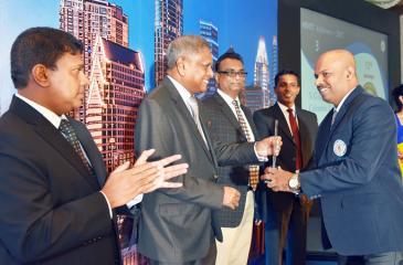 Chairman Hemaka Amarasuriya presents an award to a top performer.